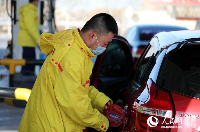 梁杨正在给顾客加油 。人民网 高嘉蔚摄
